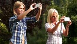 Two hot blonde bitches are outdoors flashing their perky sweet boobs