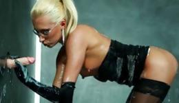 Hot blonde is blowing a fake dick through a glory hole getting wet