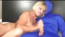 Lovely blond milf lies on the bed and licking a cock of her perverted bf